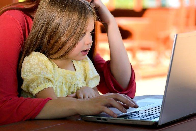 kind op schoot tijdens werk